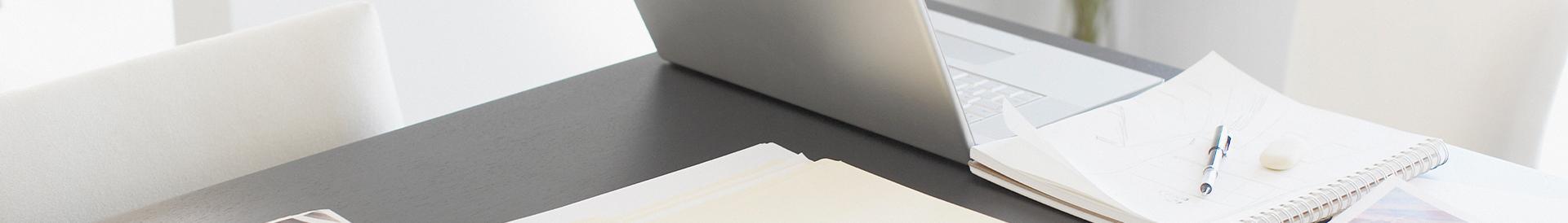 Laptop oraz papiery na szarym biurku